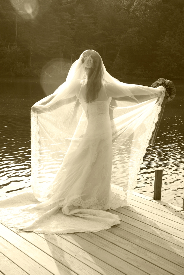 My wedding dress was a long, off white strapless lace dress with a sweetheart neckline.  I wore my Mother's wedding veil which was also long with a lace details around the edge.  I made my own jewelry - a teardrop crystal necklace on clear fishing line and matching earrings.  I also wore my Grandmother's ring.  For the ceremony I bustled the train, put on strappy heels, and removed the veil.